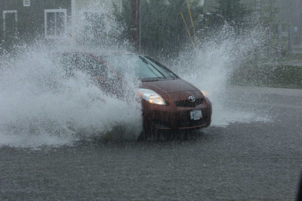 SPLASH: Like a flume, a Prius splashes through the flooded lanes of West Shore Road on Friday afternoon.