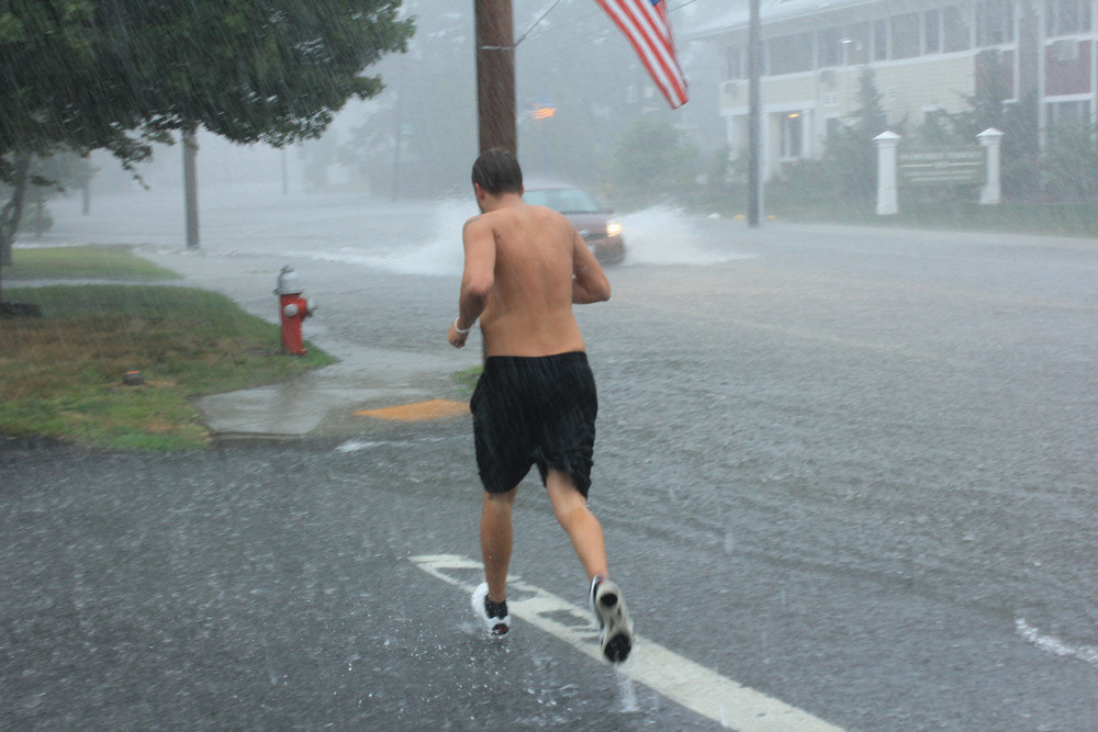 SOGGY JOG: A jogger got stranded in the downpour Friday afternoon as he tried to make his way down West Shore Road.