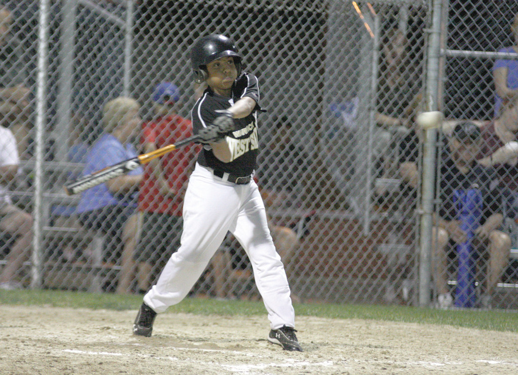 CLUTCH: West Side's Isaiah Rosa starts his swing on his inside the park grad slam in Saturday's championship.