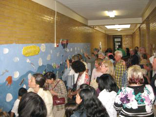 ON DISPLAY: Members of the Rhodes community view the mural that took the students most of the school year to complete.