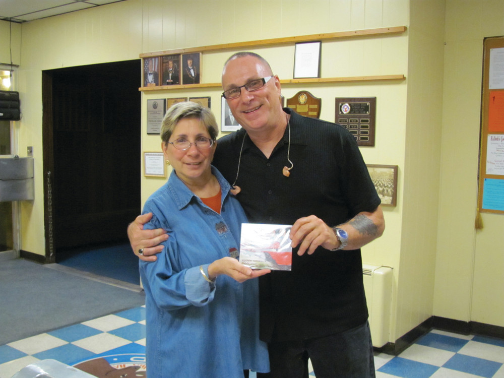 ON THE RIGHT TRACK: Donna Warner, the Exalted Ruler of the Tri-City Elks Lodge No. 14 on West Shore Road in Warwick, gets a special gift from Roger Ceresi – his group's newest CD release during last Friday's special appearance.