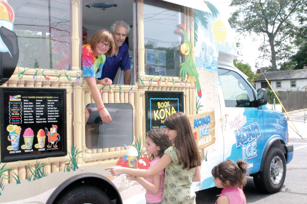 COLD TREAT, WARM SMILES: Bob and Joyce Bouchard of Smithfield serve Warwick gals Katlyn, Grace and Kylie Bernier Kona Ice, a flavored ice treat. In addition to making a business of Kona Ice, the Bouchards plan to donate a portion of the proceeds to local organizations in need, the first being the Pilgrim High School football team.