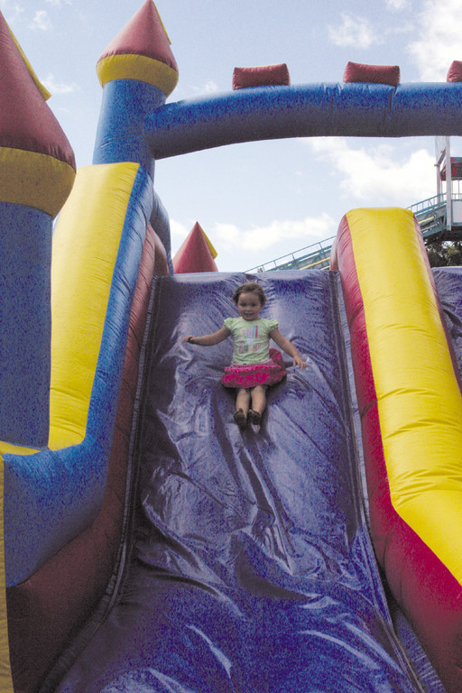 SUMMER SLIDE: Madilyn Doughty, 4, of Warwick, goes down the bouncy house slide.