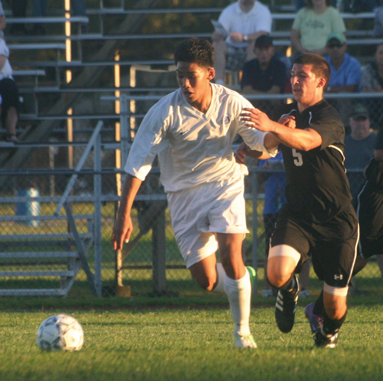 OFF AND RUNNING: Vets' Nikone Soupharath chases down the ball in the midfield as Pilgrim's Jordan DeSisto bears down.