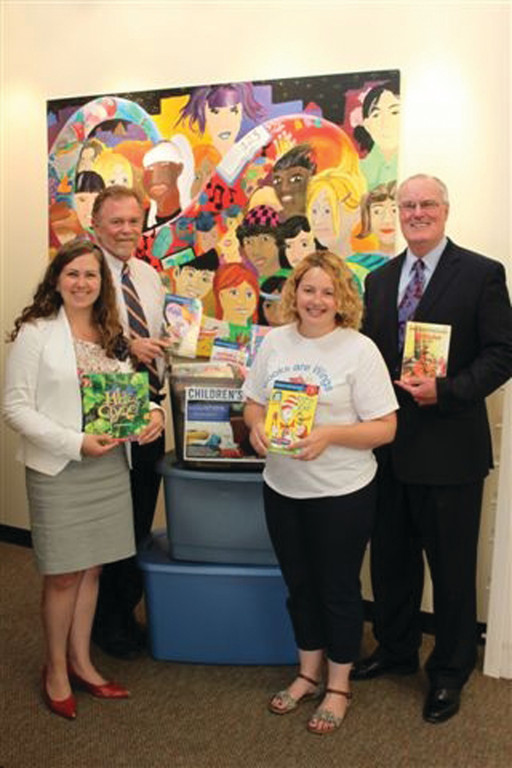 BOOKING FOR UNITED WAY: Pictured at the recent conclusion of the Washington Trust book drive are from left: Laurie Backall, major gifts & planned giving officer of the United Way of Rhode Island; Anthony Maione, president & CEO of the United Way of Rhode Island; Sarah Dennigan, assistant director of Books are Wings; and Joseph MarcAurele, chairman, president & CEO of the Washington Trust Company.