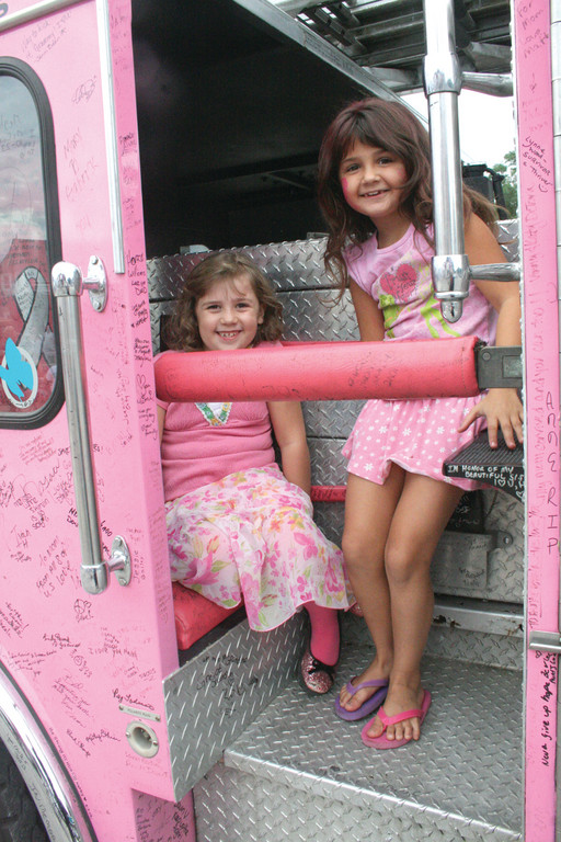 IN THE PINK: Emma Nurse and Natalie Cataldo enjoy exploring one of several pink fire trucks at Sunday's Pink Heals fundraiser at Sunny and Shears and United Ink Tattoos at 1265 Post Road.