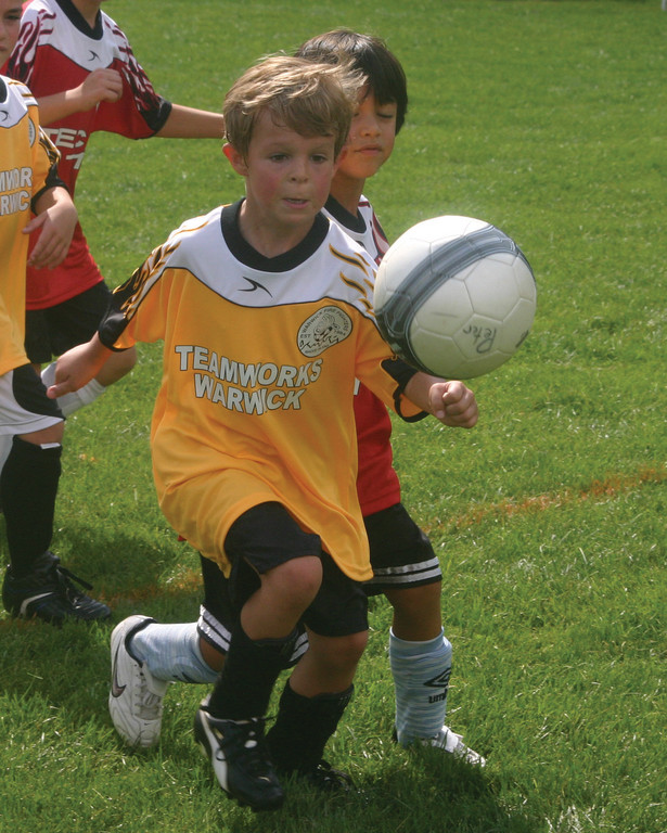 Tyler Matthews chases the ball at Fire Fighters Soccer opening day.