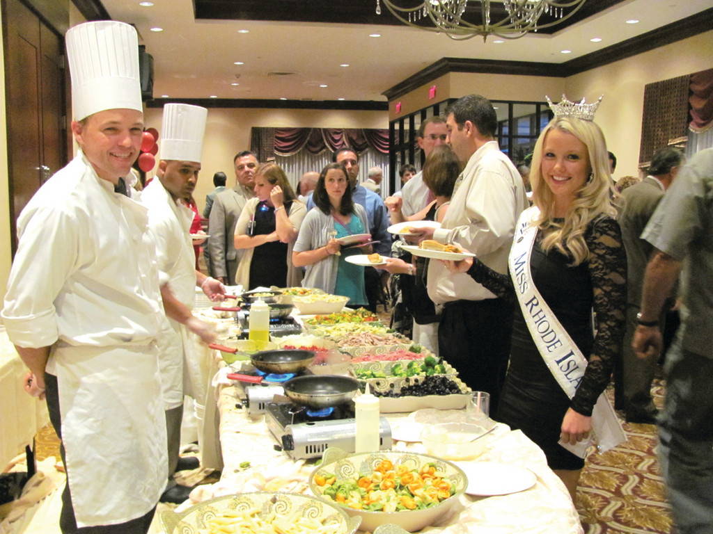 ROYAL DINNER: Kelsey Fournier, Miss Rhode Island 2012, is greeted by a Crowne Plaza chef during her stop at the Pasta Station during last Friday evening�s Rose Bids Goes to Hollywood fundraiser that benefited the Saint Elizabeth Community.