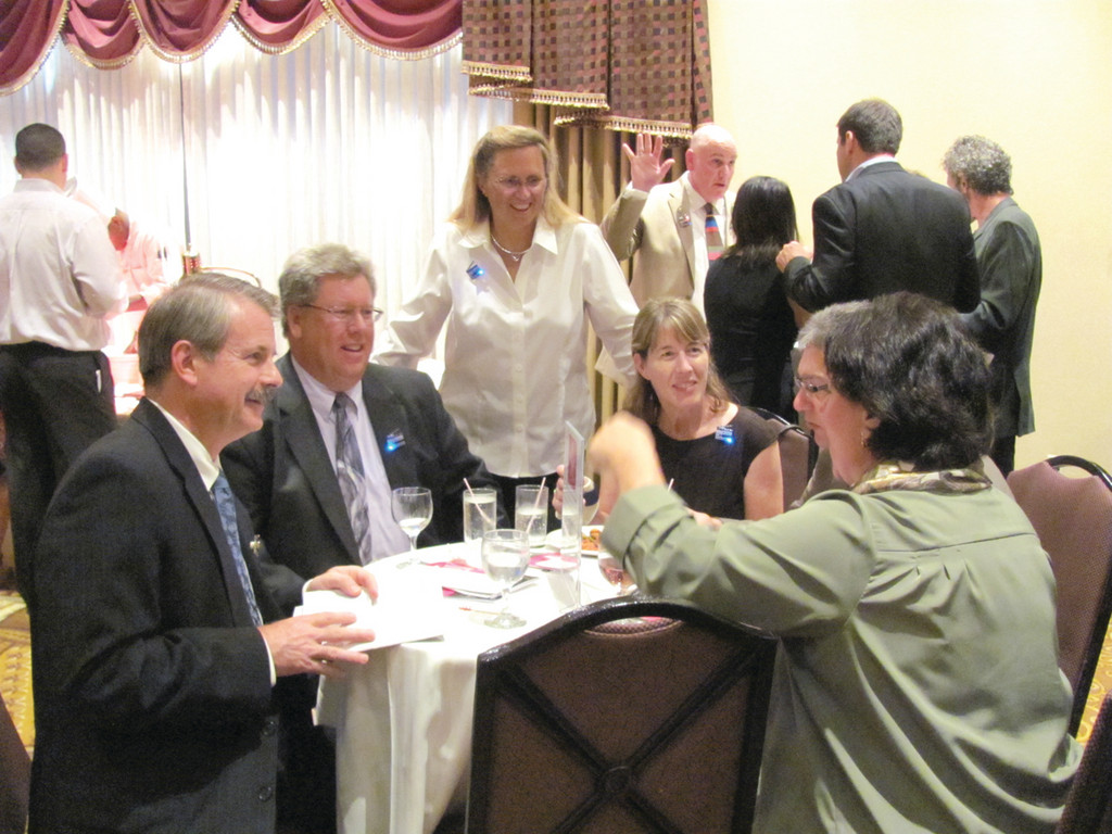 SUPPER SPONSOR: Lauren Slocum, president of the Central Rhode Island Chamber of Commerce, chats with guests at a table sponsored by her husband�s business � Slocum Realty � during last Friday night�s Saint Elizabeth Community fundraiser at the Crowne Plaza Hotel in Warwick.