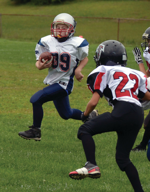 RUNNING: Eric Watts heads for the corner in Sunday's Junior PeeWee game.