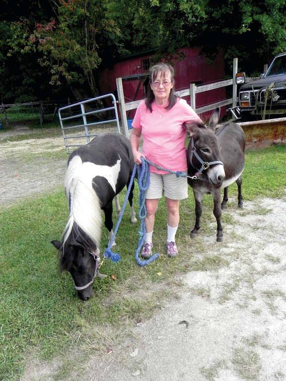ANIMAL FRIENDS: Virginia Sindelar takes Peanut and Eeyore for a walk on Grace Note Farm. Sindelar operates the place as a working farm, but most folks come to forget about their daily routine and bask in the slow moving atmosphere of the 1730 homestead and its surroundings.