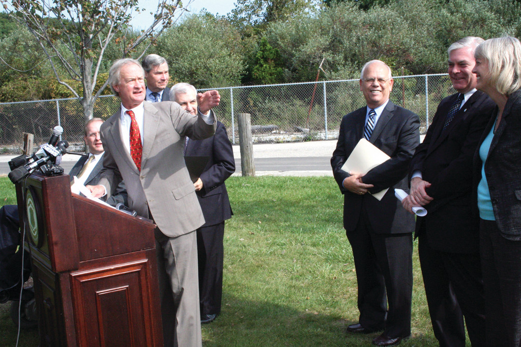 JUST OVER THERE: Governor Chafee points across the bay to Colt State Park at yesterday's announcement that an agreement has been reached for the state to buy the rest of Rocky Point.