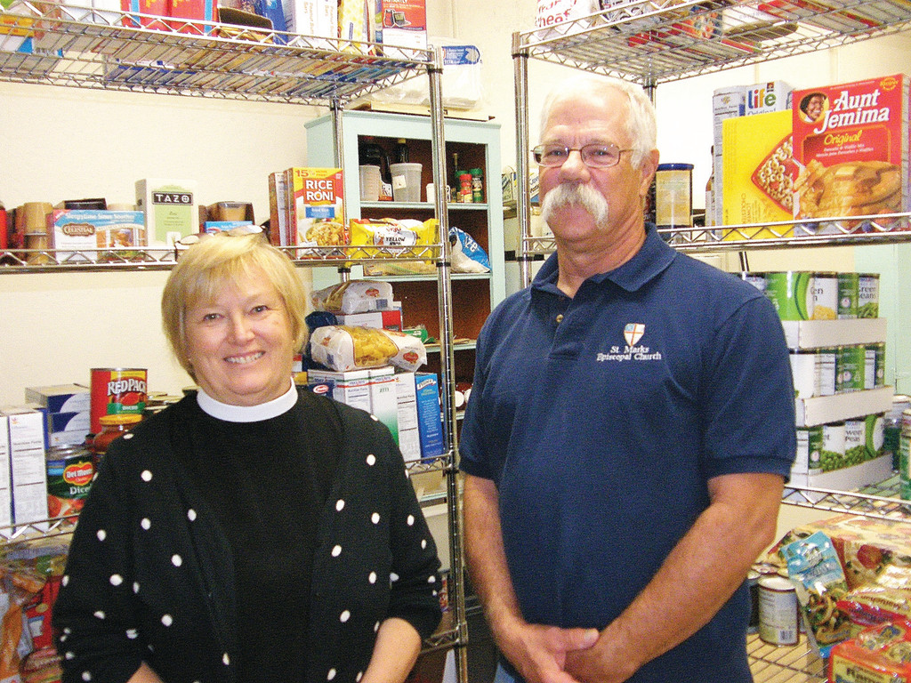 STOCKED SHELVES: Reverend Mother Susan Wrathall and Dennis Moore, co-chair of the free lunch and food pantry at St. Mark's Episcopal Church, stand in front of the church's makeshift food pantry. The pantry and free lunch take place on the last Saturday of every month, when SNAP cards are assumed to be close to depletion.