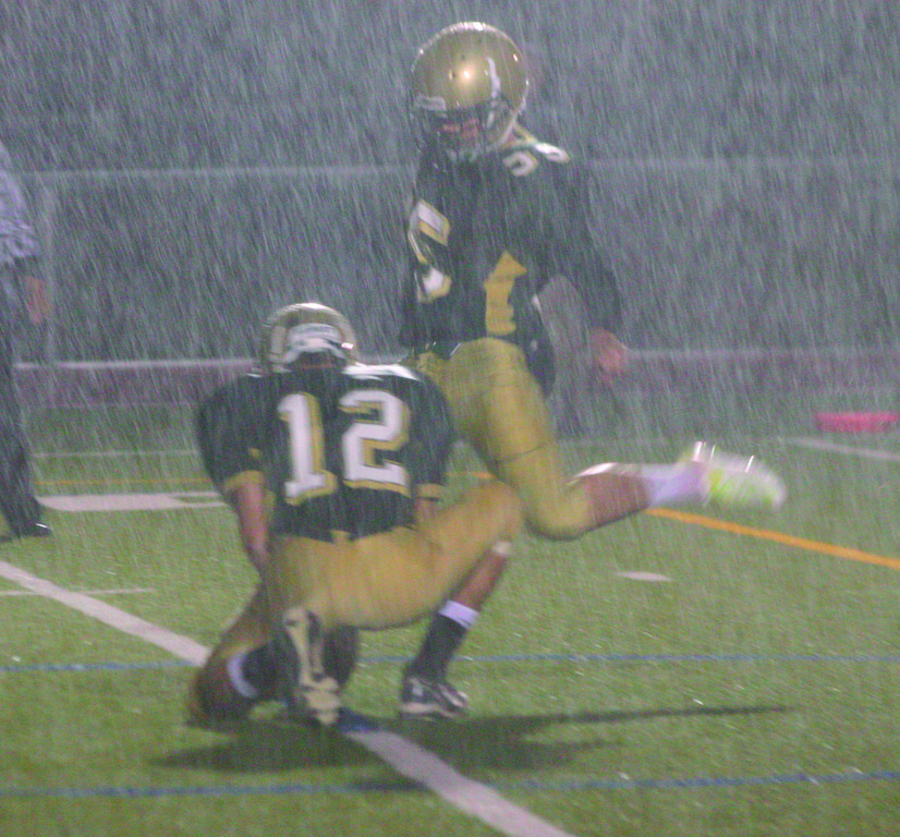Bobby Lineberger kicks an extra point in the driving rain.