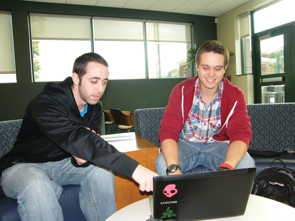 "IN THE GAME: Corey King, 22, at left, and John Groh, 20, work on their game, ""Parkourasaur,"" in the student lounge of New England Institute of Technology, where they are students. The pair, who met at the school in 2010, hope to raise $7,000 to fund the game and release it later this year."