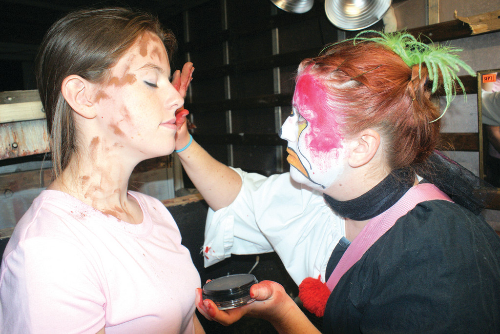 GETTING IN TOUCH WITH YOUR INNER GHOUL: Clown artist Lacey Gardner applies make-up to Keri Vanasse, prior to taking to the field at Scary Acres located at Confreda Farms.