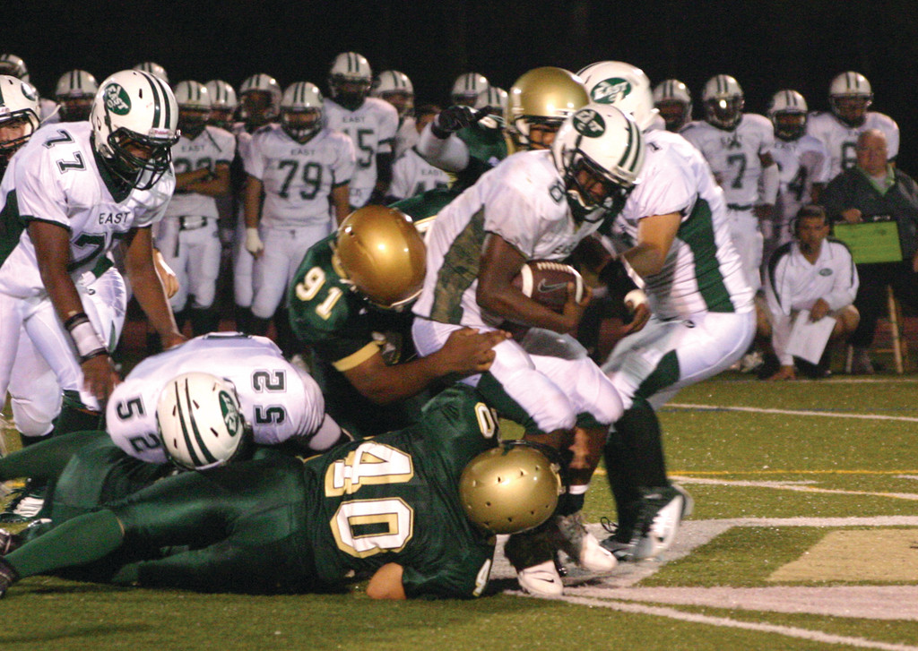 SWARM: Mario McClain and Erik Olson drag down Cranston East's E.J. Isom in last year's meeting. The Hawks defense will have its hands full this year when the unbeaten 'Bolts come to town on Friday.
