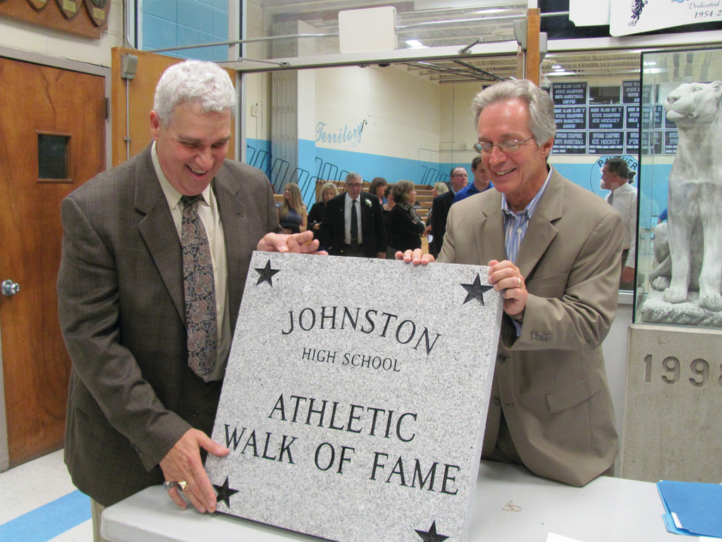 Athletic Hall of Fame founder Gary Mazzie (left) and one-time teacher coach Allan McGillivray display the Walk of Fame plaque that will soon be placed at the entrance of the Edward L. DiSimone Gymnasium.
