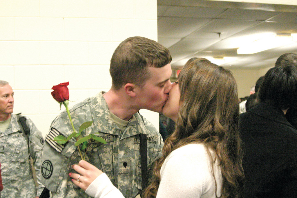 MISS YOU, WANNA KISS YOU: After being apart for nearly a year, SPC Cole Larrivee plants a big smooch on his girlfriend, Brittney Lowe.