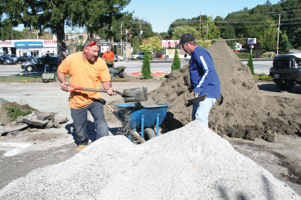 FOR A FULL LOAD: Bob Ottone and Scott Small fill a wheelbarrow.