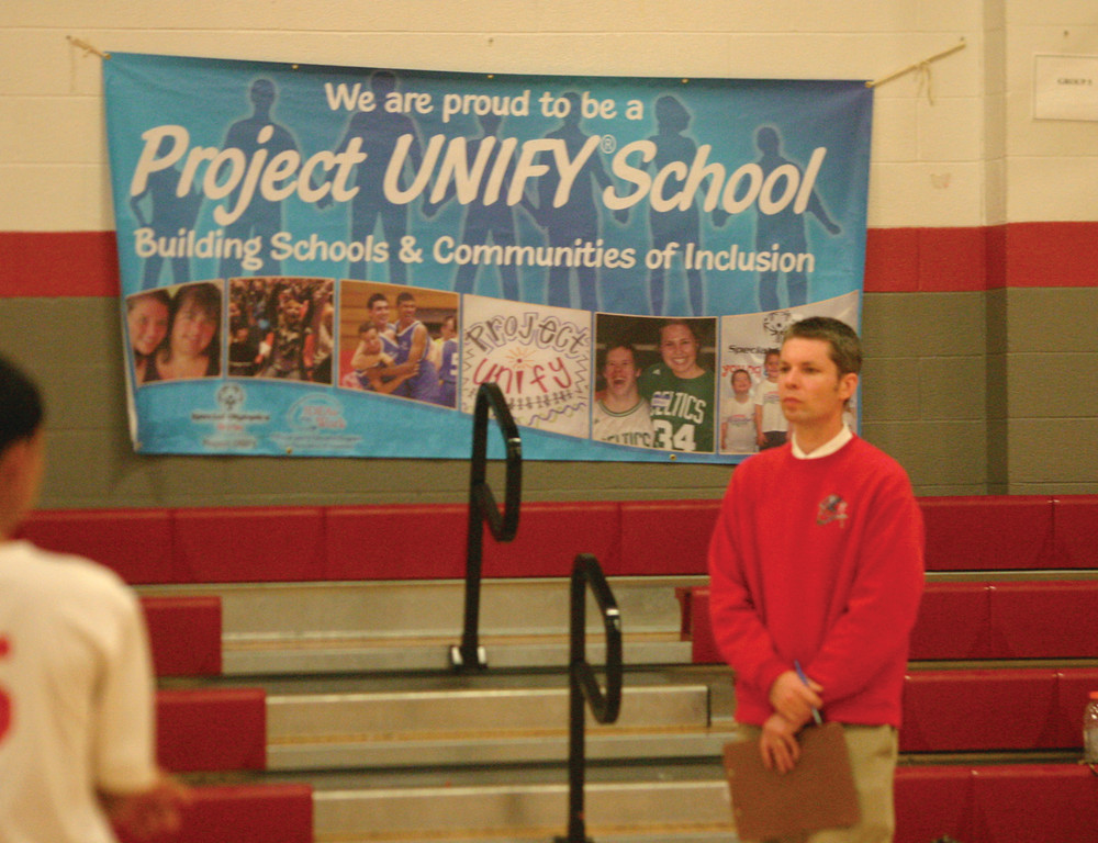 TEAMING UP: Cranston West unified volleyball coach Matt Reis watches the action in front of a banner touting Project Unify.