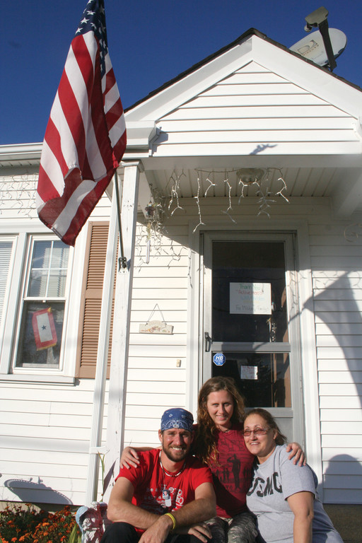 A COMMON PATH: Will Mosebach and Kristen Creech take a load off on the front steps of Cranston resident Jacqui Savattere,a military mom who opened her home to the Active Heroes Volunteers.