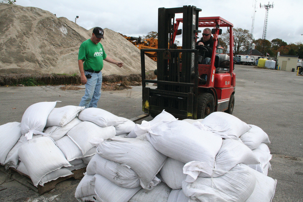 FIRST 2,000 BAGS: Sandbags were distributed from the Department of Public Works yard starting Sunday at 1 p.m., and within the first hour more than 100 had been picked up. Here, looking on as forklift driver Bob Craig delivers another pallet is Scott Small.