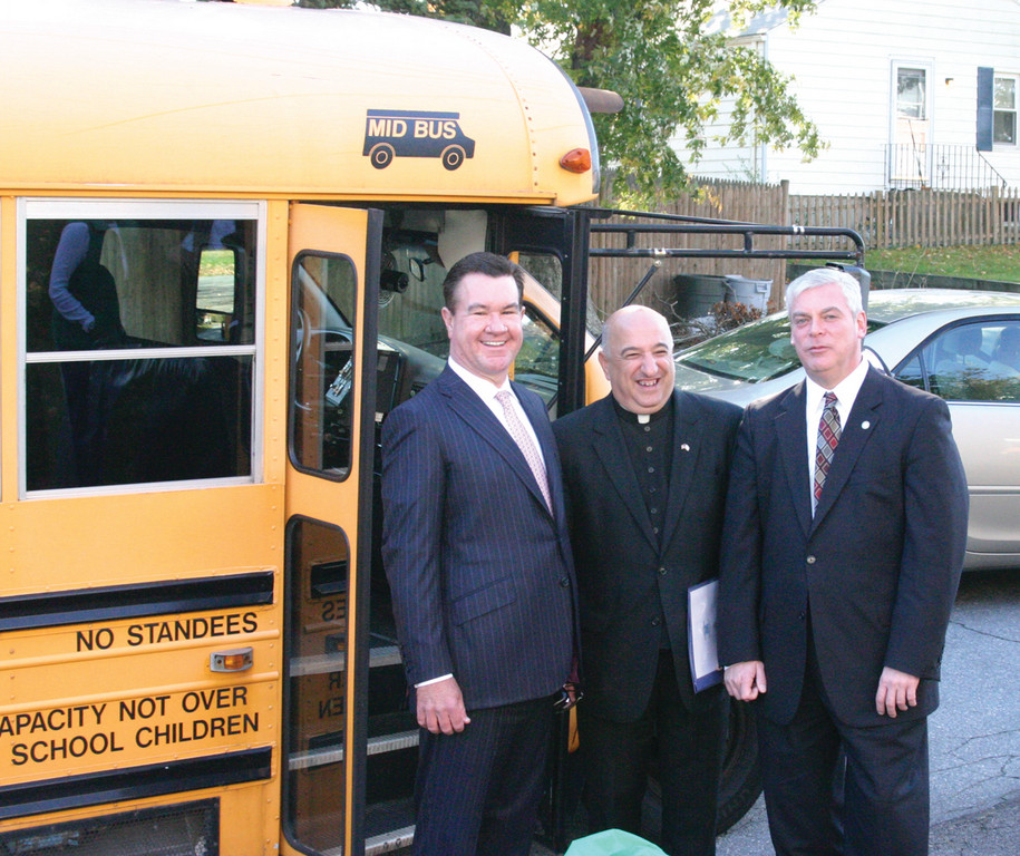READY TO RIDE: John T. Carroll, Mayor Scott Avedisian and Father Marciano stand in front of St. Kevin's new bus following a ceremony at the school on Monday.