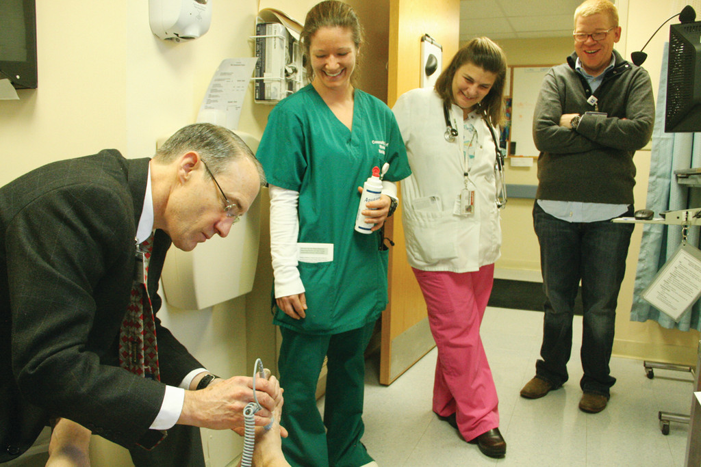 A FOOT UP: Dr. George Perdrizet, medical director at the Wound Recovery Center at Kent Hospital, with April Stevens, a nursing student at CCRI; Maria Pezzillo, CCRI assistant professor of nursing, and Jim Beardsworth of the hospital staff get a good look – maybe a whiff – of my feet during diabetes awareness day at the hospital Saturday.