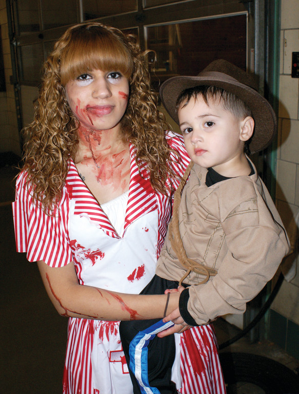 SCARY SIBLINGS: Stephanie Bagu selected a bloody nurse costume as she holds her younger brother, 3-year-old Jeremiah, who was Indiana Jones. Both attended the annual Halloween Party at the Cranston Fire Department Headquarters on Pontiac Ave. on Halloween night. The city of Cranston and the Cranston Fire Department hosted the event. The party has been an annual tradition in Cranston for decades and allows children of all ages to have a fun and safe Halloween.