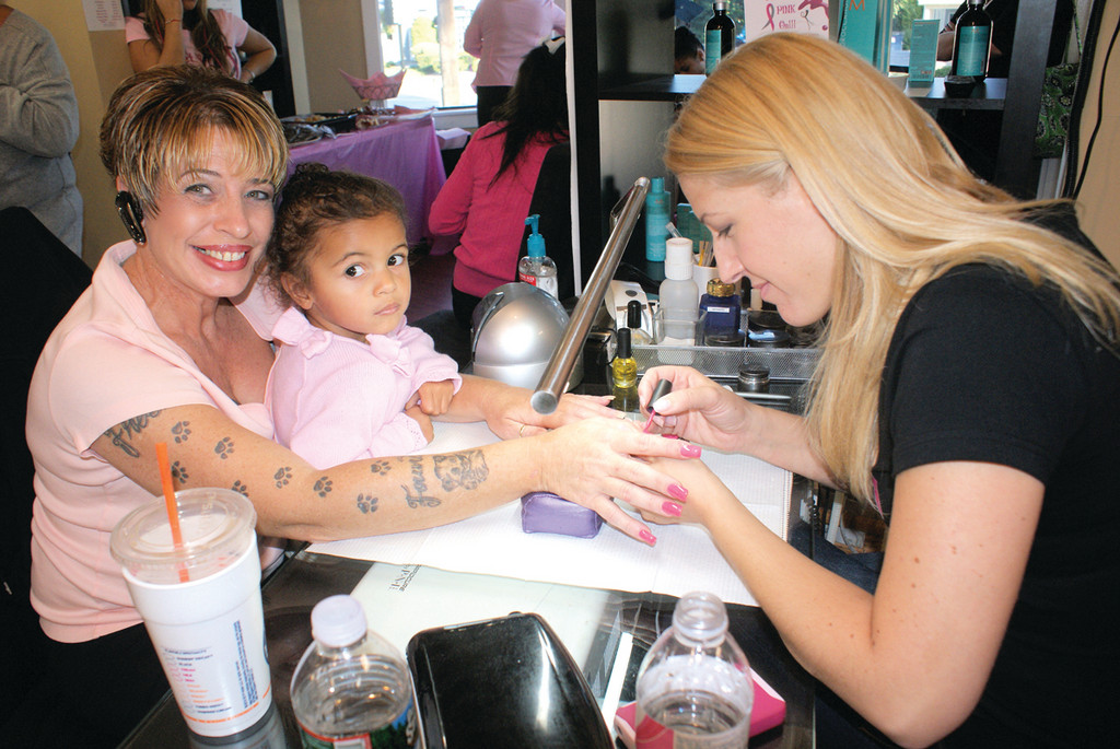 LET THE PINK SHINE: Gina Sylvestro, owner of Gel Essentialz, paints a pretty pink on LaDonna Starbeck, holding young Ariel Lietar.