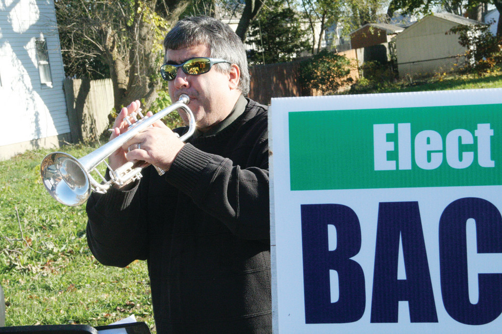 TRUMPETING HER CANDIDACY: Warwick music teacher George Landry played �God Bless America� and other patriotic songs to voters at the Shields Post Tuesday. While his music was in support of Karen Bachus for School Committee, the day had a special meaning to him. Tuesday would have been the 50th birthday of his close friend Scott Theisler, a sax player, who died at 16 in an automobile accident on Jan. 1, 1979.