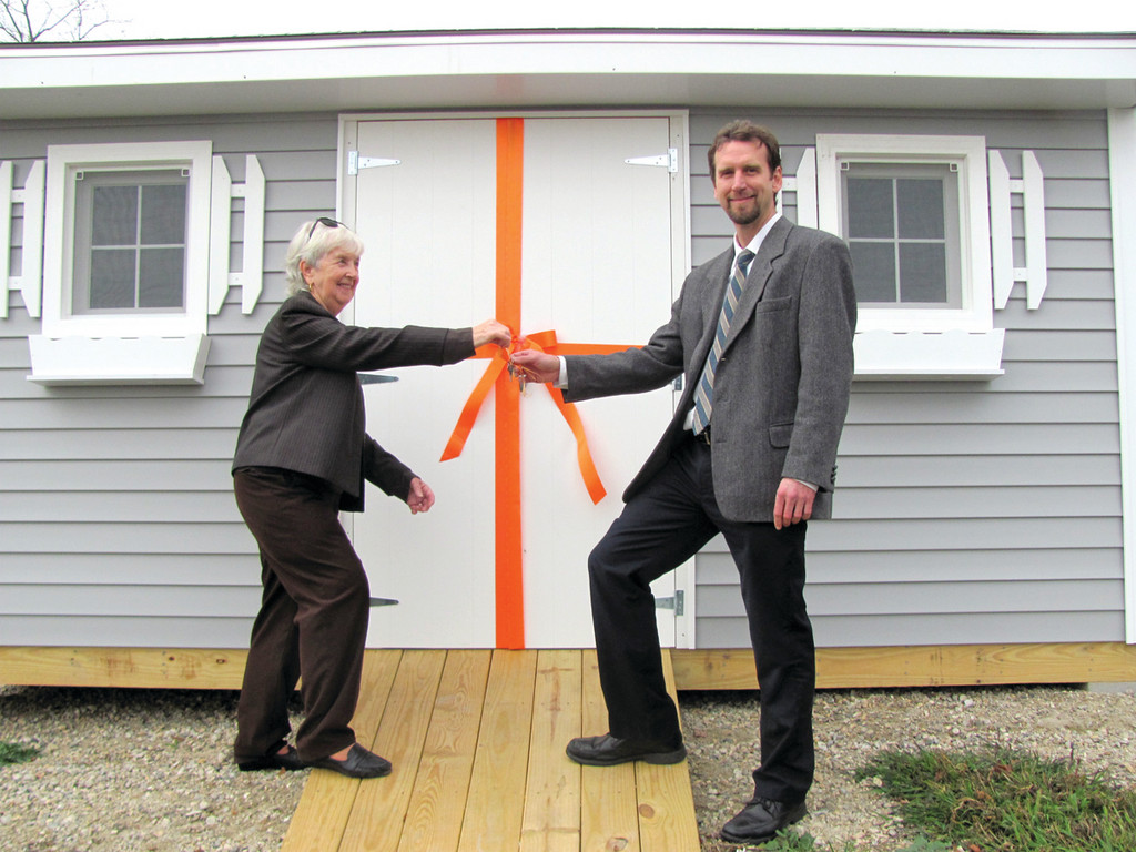 Sheila Manney, secretary of the Friends of Mohr Library, presents Marian J. Mohr Memorial Library Director Jon Anderson with the keys to a new shed that was made possible by the non-profit group and Home Depot Foundation.