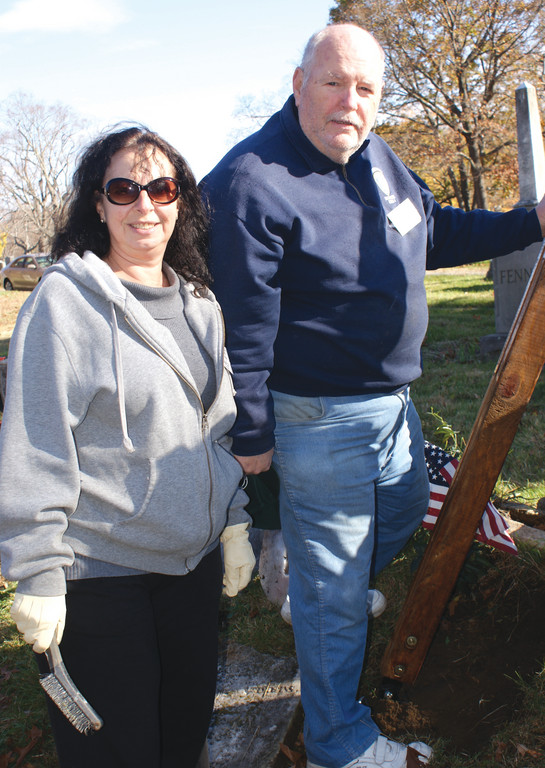 Working together, Nancy Rossi and Bill Downing assist with the resetting of broken headstones at the historical Pocasset Cemetery this past weekend.