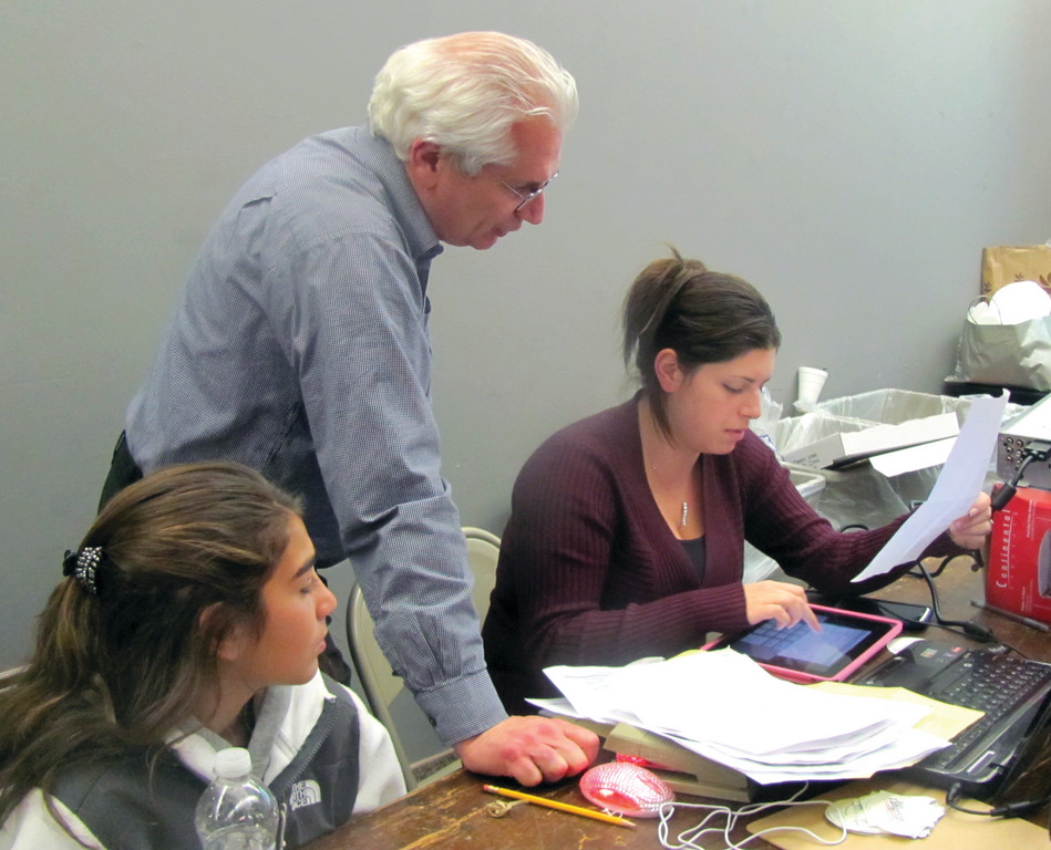 Peter DelPonte and his daughter, Christine Paulson, check numbers on a computer program that keeps track of votes as they come in.