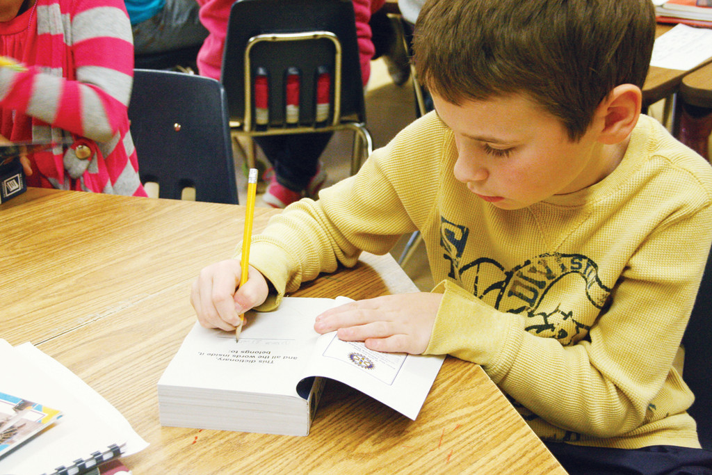ALL HIS: Oakland Beach third grader Antonio Guertin writes his name in the flap of the dictionary given him by the Warwick Rotary Club.
