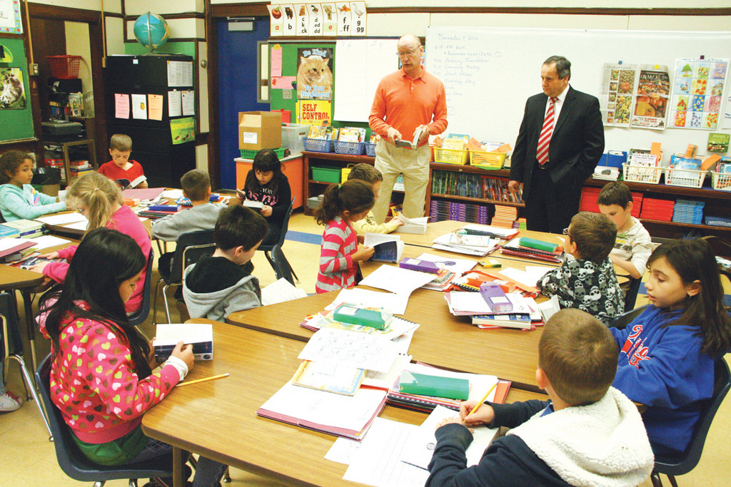 "DICTIONARY PROJECT: Warwick Rotary Club President Dennis Sleister, left, is joined by acting superintendent Richard D'Agostino at one of two Oakland Beach School third grade classes where club donated dictionaries were given out. D'Agostino told the students their dictionaries are a gift they will never out grow and ""if you use them every day they will make you smarter."""