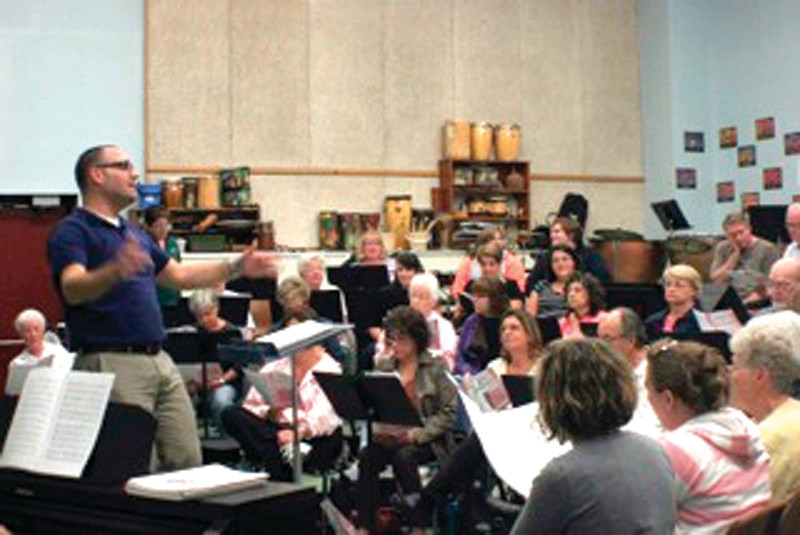 SING OUT: Nicholas Laroche directs the members of the Pawtuxet Valley Community Chorus during a rehearsal at West Warwick High School. The chorus will hold their annual Christmas concert at the school Dec. 8 and 9.