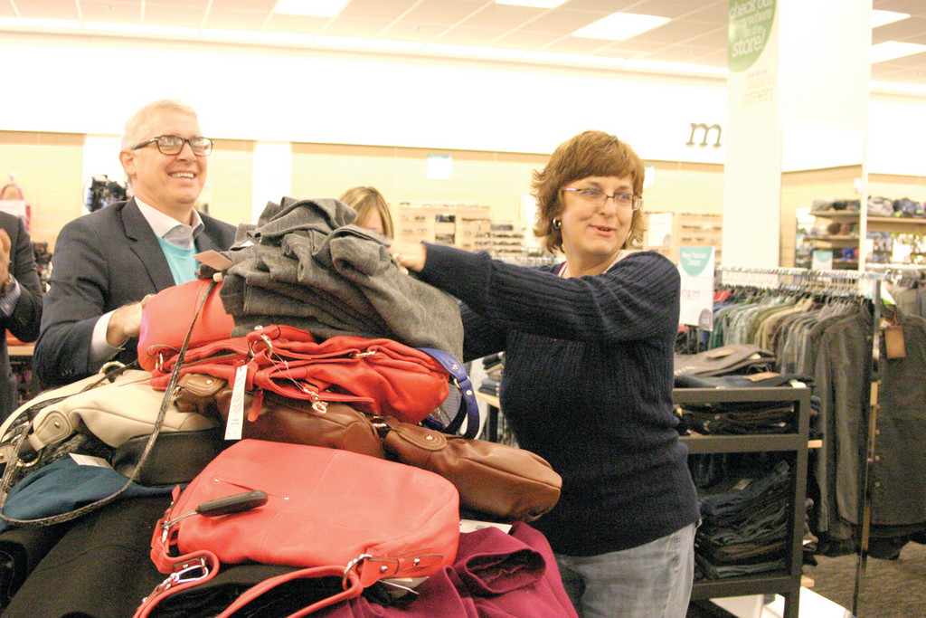 "RACE THROUGH THE RACK: As she frantically scooped items such as winter hats, gloves, coats, jeans and purses into a shopping cart, Dengal said, ""Sorry I'm making a mess."" Bob Bailey, the store manager at the Nordstrom's full-line store in the Providence Place Mall, pushed a cart for her as she shopped."