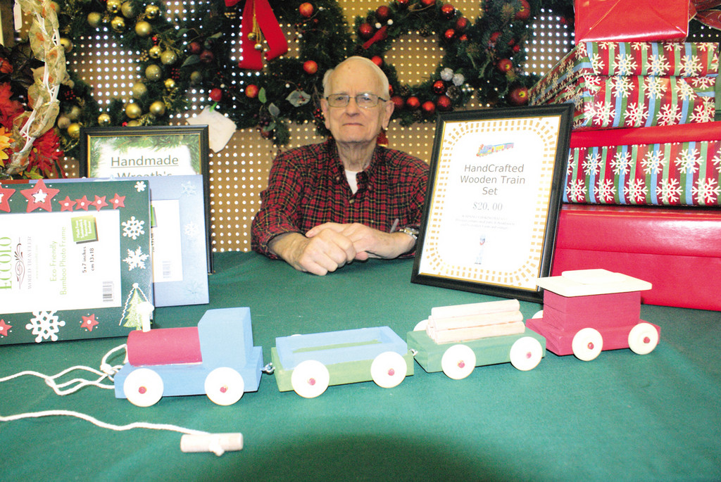 ALL ABOARD: Featuring his homemade wooden train for sale was Tom Wallace of the Woodridge Church during their annual Holiday Bazaar held this past Saturday.