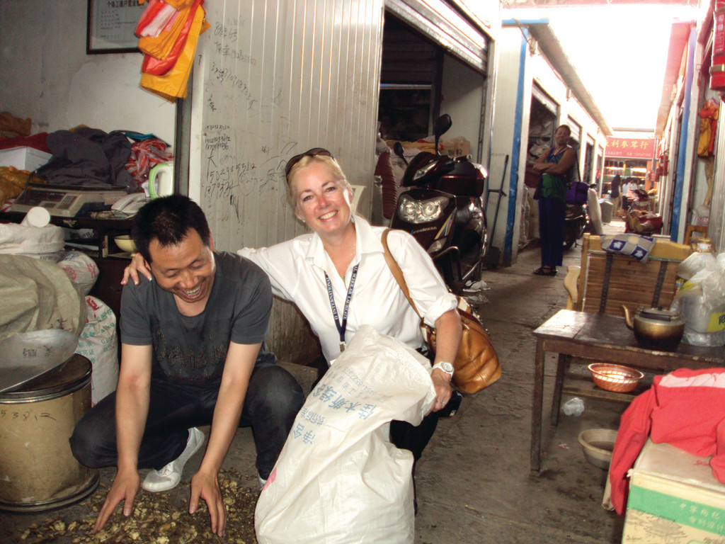 UNEXPECTED JOURNEY: URI student Angela Gasparri of Cranston hugs a vendor selling herbs in a Chinese market during an overseas study through the universitys bachelor of interdisciplinary studies program.
