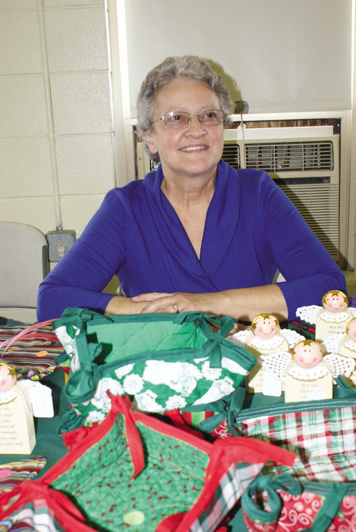 MADE WITH LOVE: Gerie DeAngelis sits at a table of handmade items including placemats, potholders and other household items for sale at the Woodridge Church Holiday Bazaar.