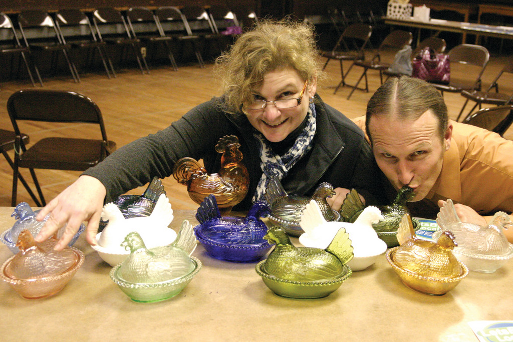CHARITY ISN'T FOR THE BIRDS: Polly Stacey of Warwick, owner of Smyle Store in East Greenwich, won a 26-piece glass chicken (and one rooster) set made by Dick Sheridan of the Ocean State Artisans at an auction recently held in support of Lets Buy Local members who had to close their store due to a health issue. Tim Hudyncia, who co-founded LBL with Lea Knepley, gives a chicken a peck.