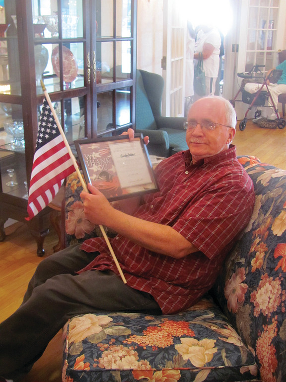 Gordon Dutra, a resident at The Bridge at Cherry Hill who served in the United States Army, holds an American flag and the certificate he received from members of the 107th Signal Company during Monday's Veterans Day salute.