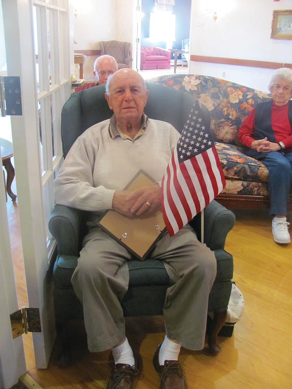 "Armando ""Casey"" Farnesi, 85, who served with the U.S. Army in the Korean War, holds his American flag during the singing of ""God Bless America."""
