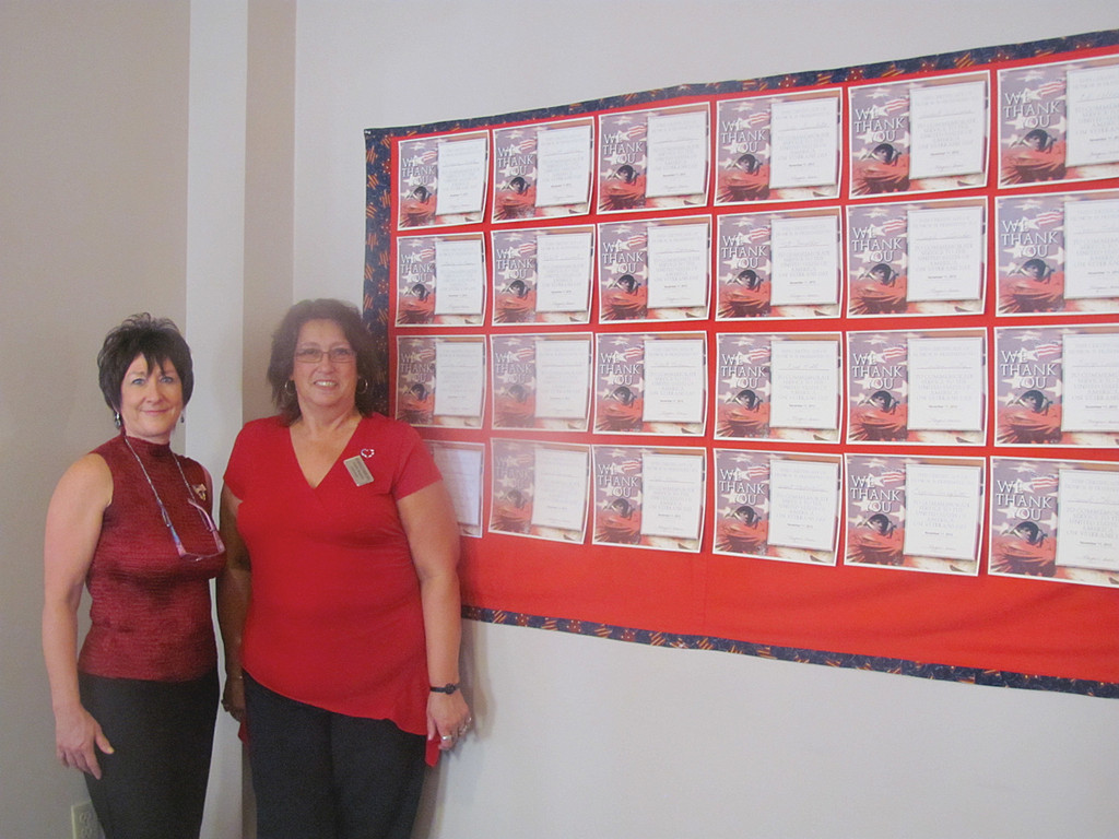 Gayle Raposa (right), the activities director at The Bridge at Cherry Hill, is joined by Sales Director Debra Demar in front of the Veterans Wall of Fame banner Raposa made especially for Monday�s salute.