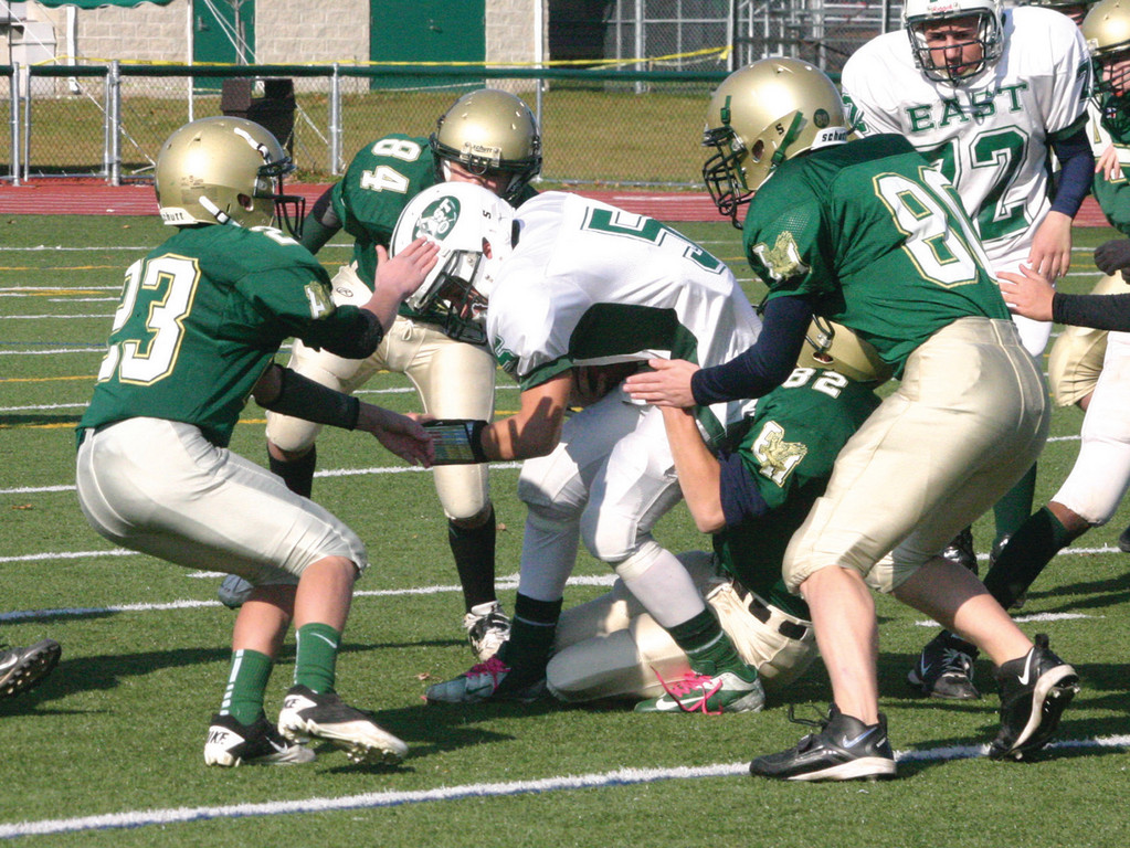 TAG TEAM: A gang of Hendricken tacklers brings down a Cranston East running back during Saturday�s freshman football semifinal game. The Hawks will be seeking their fourth freshman title in a row.