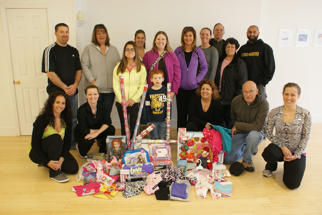 IT ALL BEGINS WITH A SPARK: Pictured is Vital Spark Fitness & Wellness Studio owner Cassandra Carlson, along with staff members, friends, family and community members who turned out to donate items for a family in need this holiday season. Donations are still being accepted at the Warwick fitness studio through Dec. 16.