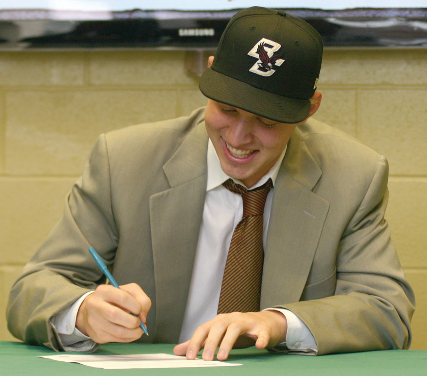 NEWEST EAGLE: Bishop Hendricken pitcher Mike King signs his letter of intent to play baseball at Boston College.