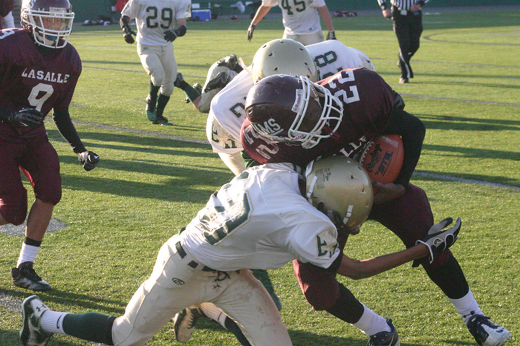 MAKING PLAYS: Hendricken's Jake Derderian and Justin Gist tackle La Salle running back T-boy White along the sidelines.